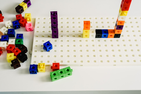 Montessori material, game to learn addition, made in colorful plastic blocks, inside a Montessori classroom. Imagens