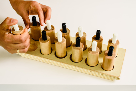 Wooden push-buttons in a montessori classroom pulsed by the teacher to demonstrate performance.