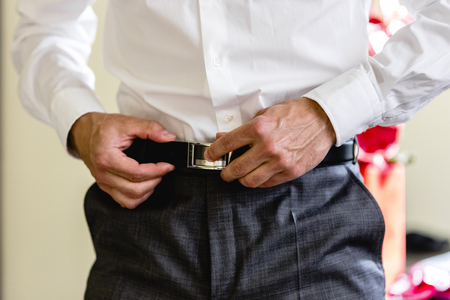 Man fastening his belt to his pants 版權商用圖片