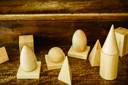 Solid wood shapes to study geometry and volumes, cones, triangles, squares, spheres on a warm wood background. Imagens
