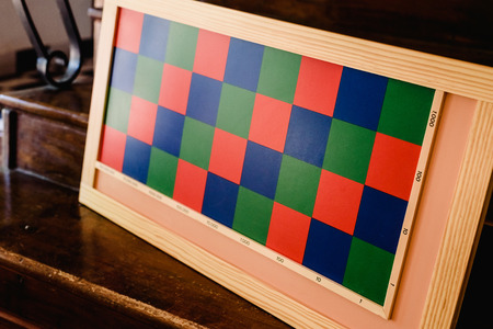 Game to learn to count, made of blue and red wood, inside a classroom montessori.