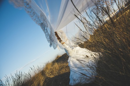 Bride in the countryside playing with the veil of her dress, moving it to the wind to have fun.