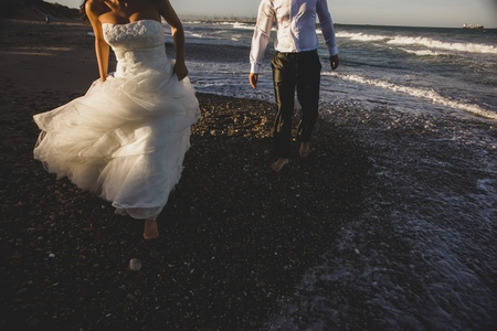 Newlywed couple, bride and groom walking on the beach. Banco de Imagens - 114329777