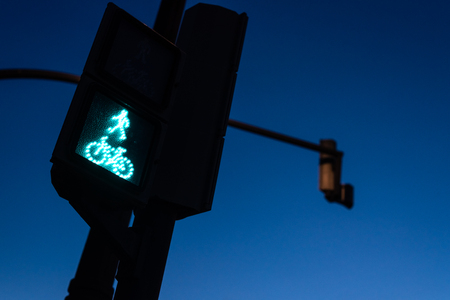 Traffic light in green for pedestrians and cyclists, with the figure of a cyclist. Night background for the concept of freeway and permission to continue.