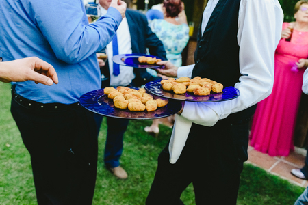 Waiters offering snacks to people who catch them with their hands at a social event