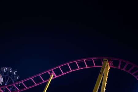 Rails of a roller coaster, blue night sky background. Фото со стока