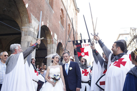 Milan, Italy - May 9, 2014: Newly-wed couple is entertained by group of men disguised as medieval times.