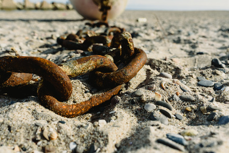 Concept of abandonment, old rusty and broken chains thrown in the sand of a dirty beach.