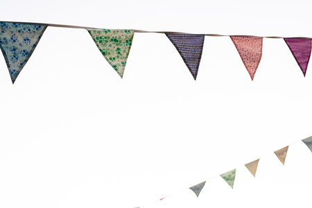 Pennants with blue sky background and pale colors hanging on a rope crossing the image during an outdoor event, space for text.
