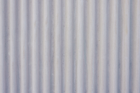 Wavy metal background on a gray wall.