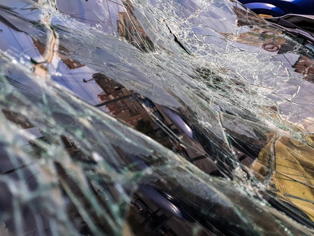 Broken windshield of abandoned and destroyed car, with broken glass.