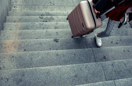 Woman dragging a trolley suitcase to climb the stairs of a subway.