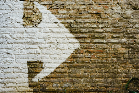 Brick wall with big white arrow indicating direction, background with copy space. Stock Photo