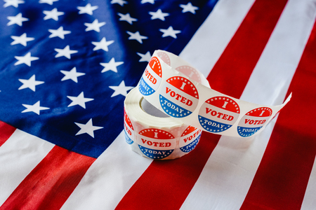 I vote today stickers roll, in US elections on American flag. 版權商用圖片