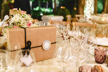 Gift box wrapped in paper and with bow and empty label to include free text, on the elegant table of the reception of a wedding, without anyone. Imagens