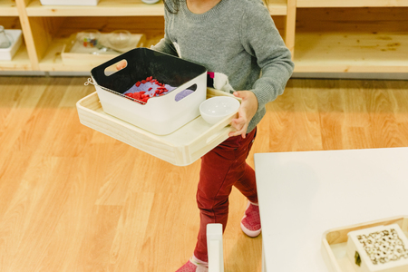 Girl in her montessori school moving trays with material from one shelf to another, concept of child autonomy. Stock Photo