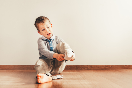 Child with lots of independence sitting on the floor putting on his socks with an expression of effort
