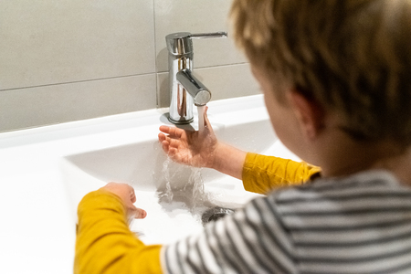 Responsible child cleaning his hands in a sink. Archivio Fotografico