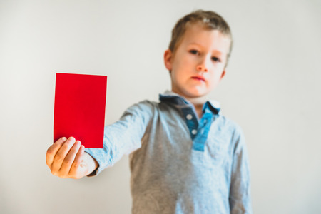 Angry face child showing a red card as a warning, stop bullying concept, blank background. Stockfoto