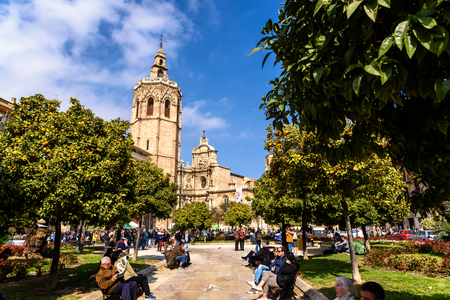 Valencia, Spain - February 24, 2019: Plaza de la Reina a sunny spring day during Fallas, with the Cathedral of Valencia and its tower Miguelete.