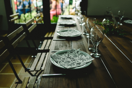 Wooden tables with cutlery plates and backlit glasses without anyone. Imagens
