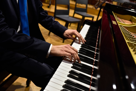 Professional pianist performing a piece on a grand piano.
