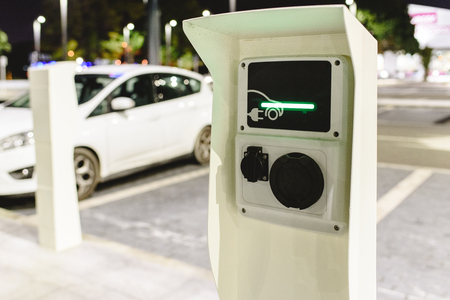 Public post charger of electric vehicles placed in the parking lot of a supermarket.