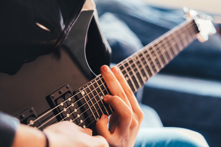 Detail of the fingers of a guitarist playing a chord on an electric guitar. Stock Photo