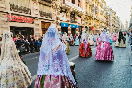 Valencia, Spain - March 17, 2019: Fallera Commission parading down Calle de la Paz, seen from behind, during the Fallas offering. Редакционное
