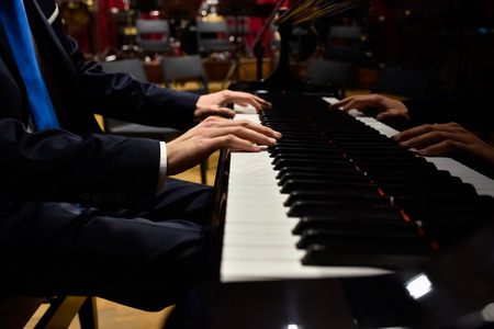Male pianist playing classical music on a grand piano. Stockfoto