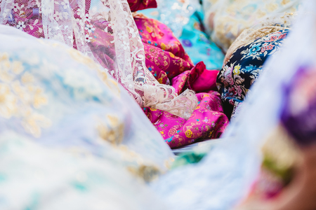 Detail of the traditional Spanish Valencian Fallera dress, colorful fabrics with intricate embroidery.