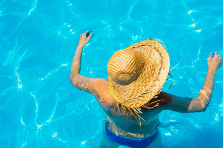 Woman in a pool with hat relaxed and rested. 免版税图像