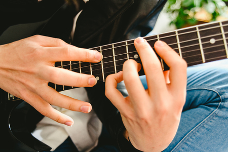 Detail of the fingers of a guitarist placed on the fret of the mast of the guitar playing a chord doing Tapping. Reklamní fotografie