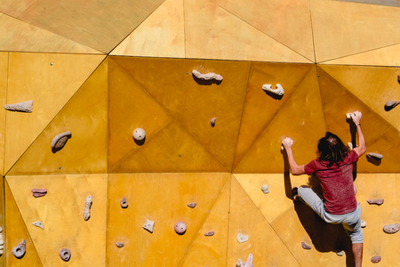 Male climber trying a complicated route to the sun on an outdoor climbing wall Stock Photo