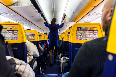 Valencia, Spain - March 8, 2019: Stewardess inside a Ryanair plane securing the top luggage before takeoff, walking down the aisle from behind. Editorial