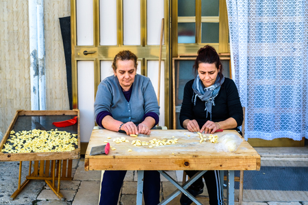 Bari, Italy - March 8, 2019: Artisan women preparing at the door of their house in the Italian city of Bari the traditional ear-shaped pasta, called orecchiette, made with flour and salt water, and folded in the street.