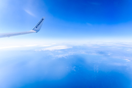 Valencia, Spain - March 8, 2019: Flaps of an Ryanair airplane seen from inside during a flight over the clouds of the sky.