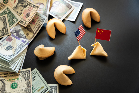concept of commercial war between USA and China, with dollar bills and flags of the capitalist countries and biscuit.