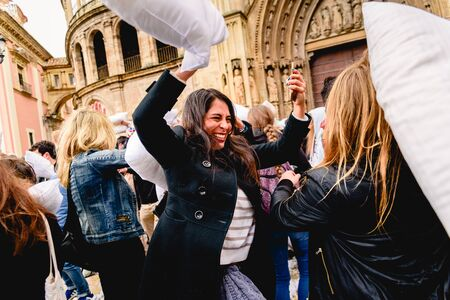 Valencia, Spain - April 6, 2019: Group of young people having fun beating each other with pillows outdoors during a party in a public square of the city. Editoriali
