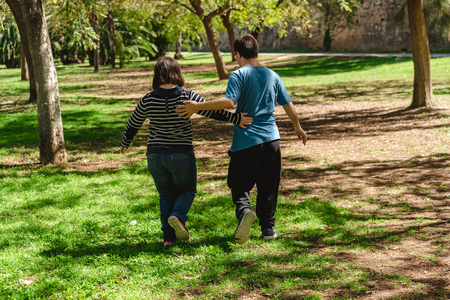 Two young men and women with Down syndrome walking on their backs holding hands giving each other mutual affection. Editorial