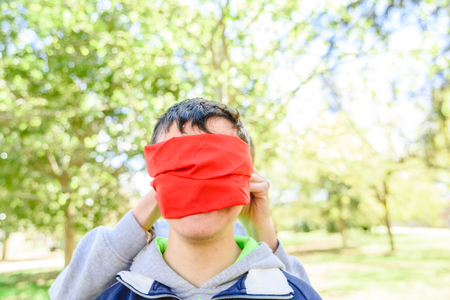 Young man with disability blindfolded by a handkerchief, concept of trust and care.