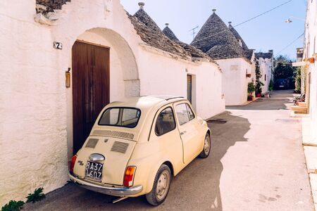 Alberobello, Italy - March 9, 2019: Old Fiat 500 car parked at the door of a house between Italian trullis. 新闻类图片