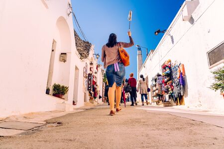 Alberobello, Italy - March 9, 2019: Tourist guide guiding a group of visitors from the beautiful city of Alberobello travel. Editorial