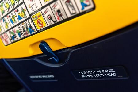 Bari, Italy - March 8, 2019: Notice of fastening the seat belt on the back of an airplane seat.
