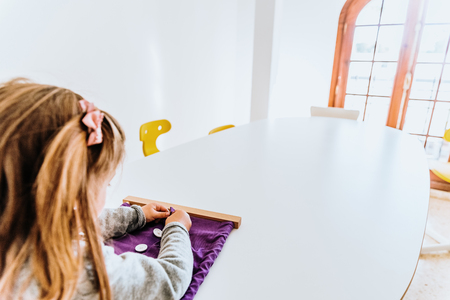 Girl buttoning a montessori frame to develop the dexterity of her fingers.
