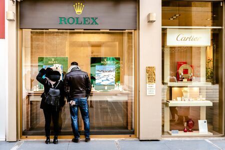 Bari, Italy - March 12, 2019: Couple in front of a showcase of the luxurious Rolex watch and jewelry store