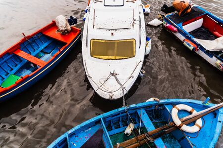 Bari, Italy - March 12, 2019: Old fishing boats moored to port dirty and in disuse.