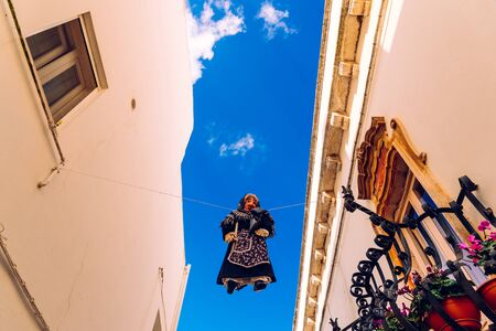 Locorotondo, Italy - March 9, 2019: Ancient ritual with witch-shaped dolls are suspended high across the streets of the Italian city of Locorotondo, on Easter, the witches are burned.