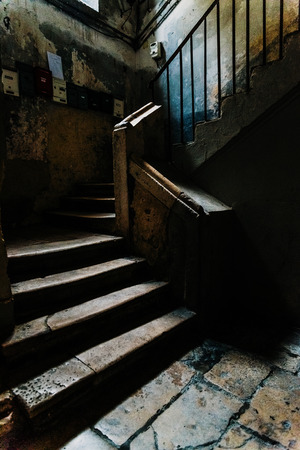 Old stone stairs in the dark atrium of a disused building in the old part of Bari, Italy.