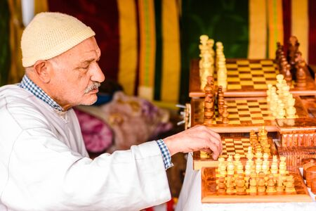 Valencia, Spain - January 27, 2019: Moroccan Arab craftsman selling pieces and chess boards made of wood by hand in a medieval market.